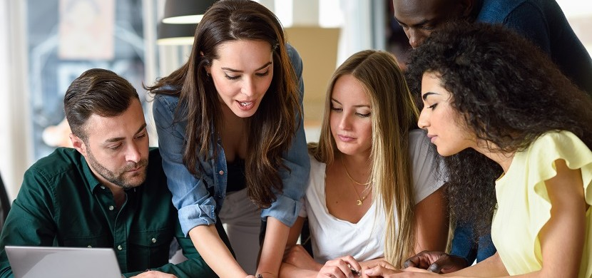 Five young people studying on white desk. Beautiful women and men working together wearing casual clothes. Multi-ethnic group.